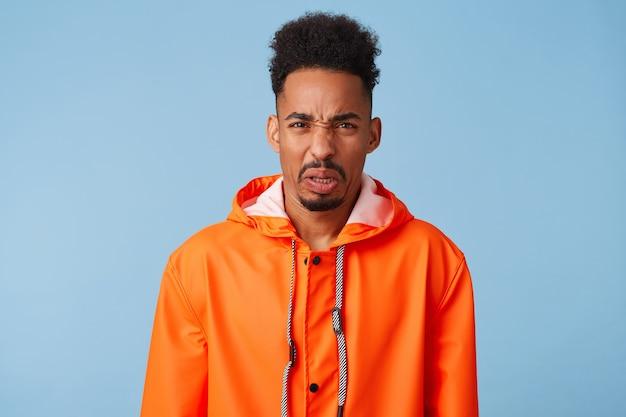 外の雨の天気に不満を持って、オレンジ色のレインコートを着て、眉をひそめている、嫌悪感のある幸せな若いアフリカ系アメリカ人の暗い肌の男のクローズアップ。