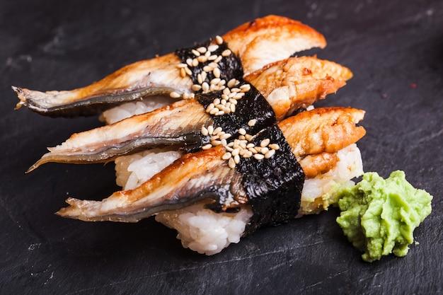 黒いスレートの背景にうなぎとわさびを添えたうなぎ寿司のクローズアップ