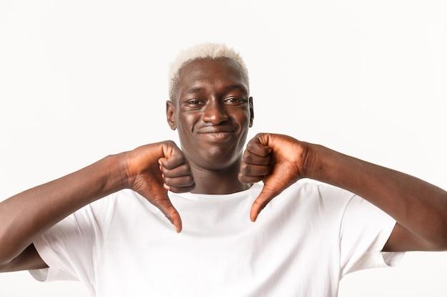 금발 머리를 가진 재미없고 회의적인 흑인 남자의 근접 촬영, 엄지 손가락을 아래로 표시하고 싫어함으로 능글 맞은 웃음, 나쁜 것은 승인하지 않음