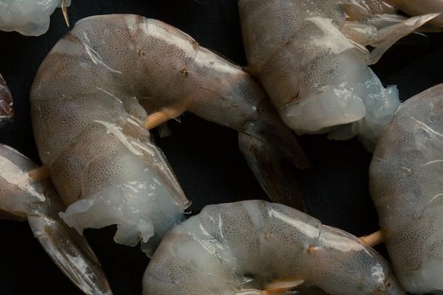 木製の串に刺した未調理の新鮮なヘッドレスタイガーエビのクローズアップ