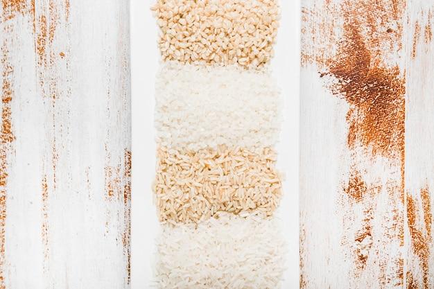 素朴な背景の上に白いトレイで生の米のクローズアップ