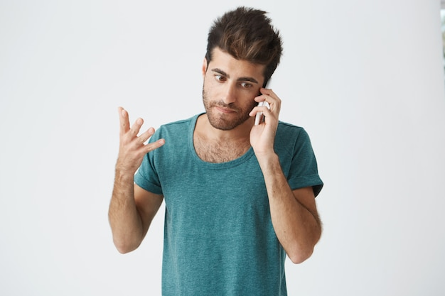 青いtシャツを着ている不幸な成熟した白人男が母親との電話での議論中に腹を立てているのクローズアップ。否定的な感情。