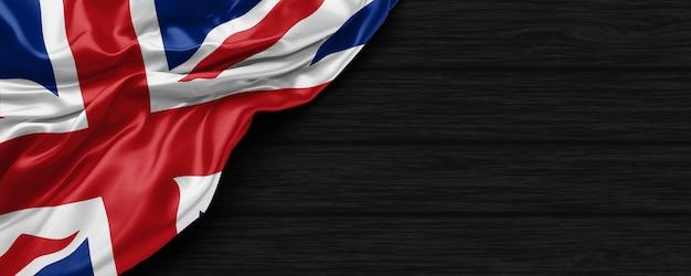 黒い木製の背景の3dレンダリングでイギリスの旗のクローズアップ
