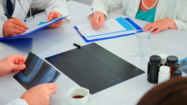 회의실에서 의료 브리핑을 하는 동안 함께 일하는 알 수 없는 의사들의 클로즈업. 질병에 대해 동료와 이야기하는 클리닉 전문 치료사, 의학 전문가