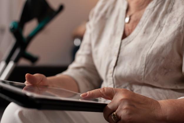 Закройте до неузнаваемости пожилых рук, касаясь экрана планшета дома