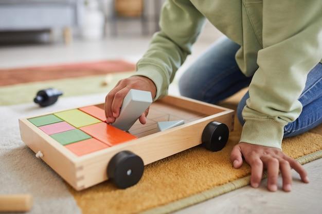 Крупным планом неузнаваемого афроамериканского ребенка, играющего с игрушками, сидя на полу дома, скопируйте пространство