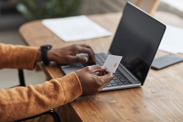 Крупный план неузнаваемого афроамериканца, держащего макет кредитной карты во время покупок в интернете через ноутбук, копирование пространства