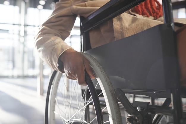 Крупным планом неузнаваемого афроамериканца, использующего инвалидную коляску во время транспортировки в городском городе, с акцентом на руке на колесе, копией пространства