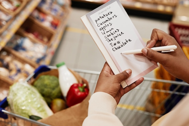Крупным планом неузнаваемой афроамериканской женщины, держащей список покупок при покупке еды в супермаркете, копией пространства
