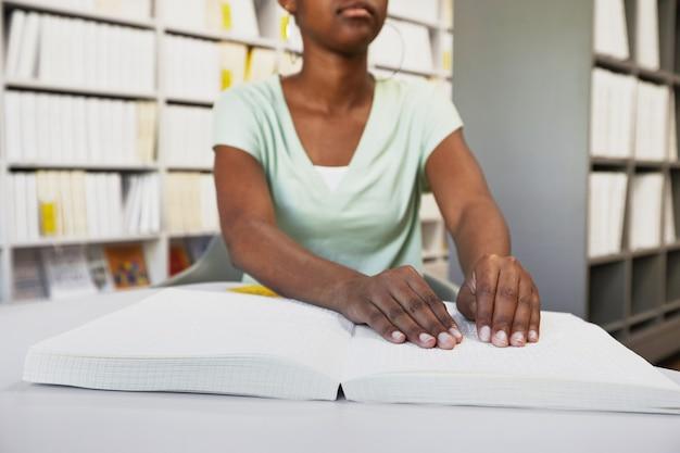 大学図書館のコピースペースで点字の本を読んで認識できないアフリカ系アメリカ人の女性のクローズアップ