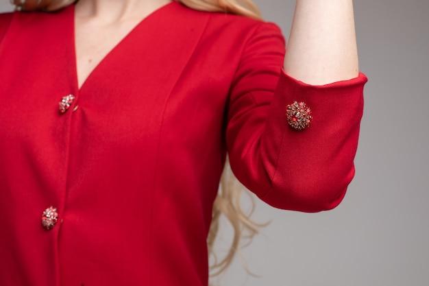 真っ赤なジャケットまたは美しい宝石のボタンが付いているドレスの認識できない金髪の女性のクローズアップ。