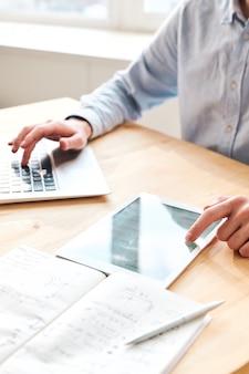 Крупный план неузнаваемого бизнесмена, сидящего за столом и использующего устройства во время изучения онлайн-данных