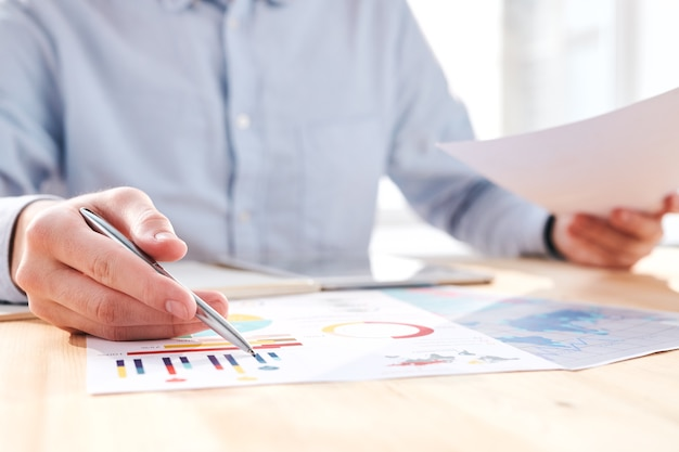 Крупный план неузнаваемого бизнесмена, сидящего за столом и обсуждающего бизнес-диаграммы на встрече