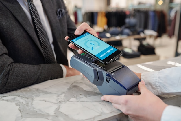 인식 할 수없는 사업가 매장의 카운터에 서서 온라인으로 스마트 폰으로 지불하는 클로즈업