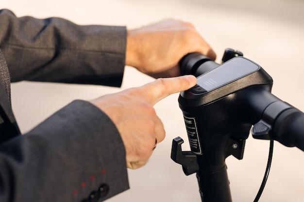 Крупный план неузнаваемого бизнесмена включает электрический самокат, мужчина нажимает кнопку пуска