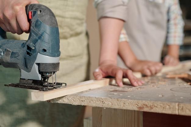 板を保持し、ワークショップでそれを切断しながらジグソーを使用して認識できない大工のクローズアップ