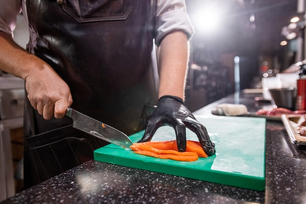 カウンターに立って、業務用厨房の調理台でサーモンを切るエプロンの認識できないシェフのクローズアップ