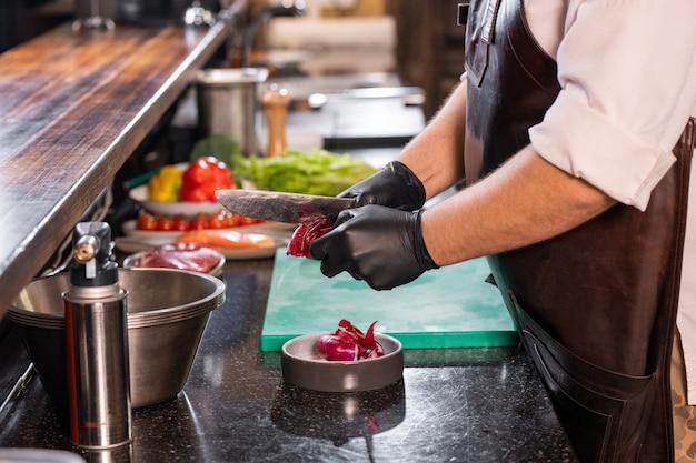 業務用厨房で赤玉ねぎをはがしながらナイフを使ってエプロンで認識できないシェフのクローズアップ
