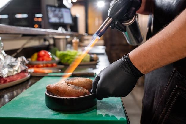 레스토랑 주방에서 고구마를 요리하기 위해 가스 토치를 사용하는 검은 장갑에 인식 할 수없는 요리사의 근접