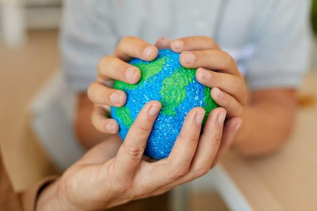 Крупным планом неузнаваемого ребенка, держащего модель планеты во время учебы дома с матерью или репетитором, копией пространства