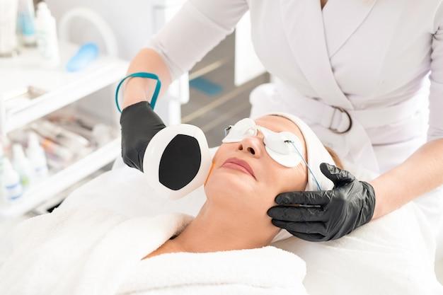 Крупный план неузнаваемого косметолога в латексных перчатках, делающего антивозрастную лазерную процедуру зрелой женщине в защитных очках