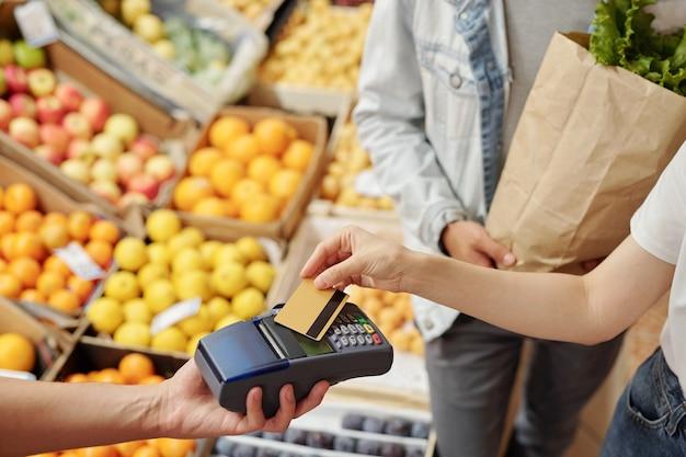 ファーマーズマーケットで非接触型決済を使用しているときに端末にワイヤレスカードを置いている認識できない顧客のクローズアップ