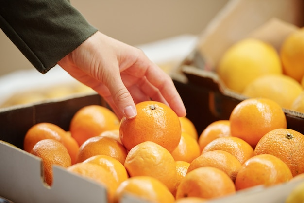 Крупный план неузнаваемого покупателя, касающегося мандарина в коробке, выбирая его для покупки в магазине
