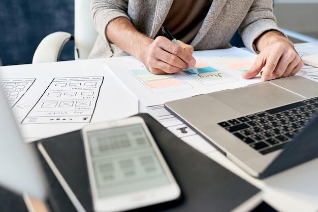 인식 할 수없는 디자이너가 장치와 함께 책상에 앉아 전화 설계 계획에 포스트잇 메모를 작성하는 클로즈업