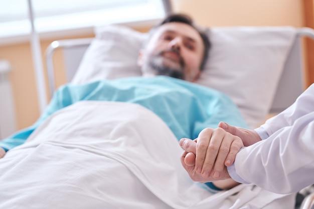 外科手術の前に彼をサポートしながら患者の手を握っている認識できない医師のクローズアップ