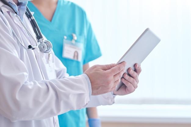 Крупный план неузнаваемого врача в лабораторном халате, использующего планшет во время обсуждения информации о пациентах онлайн с медсестрой в больнице