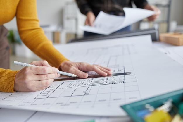 사무실에서 책상에서 작업하는 동안 인식 할 수없는 여성 건축가 도면 청사진의 닫습니다,
