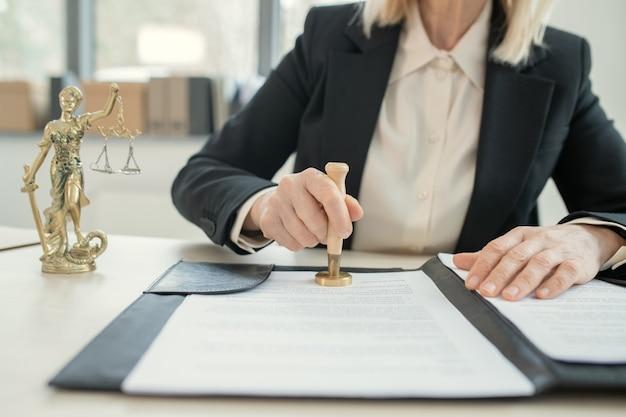 테미스 법령과 스탬프 문서가 있는 책상에 앉아 있는 검은 양복을 입은 알아볼 수 없는 여성 변호사의 클로즈업