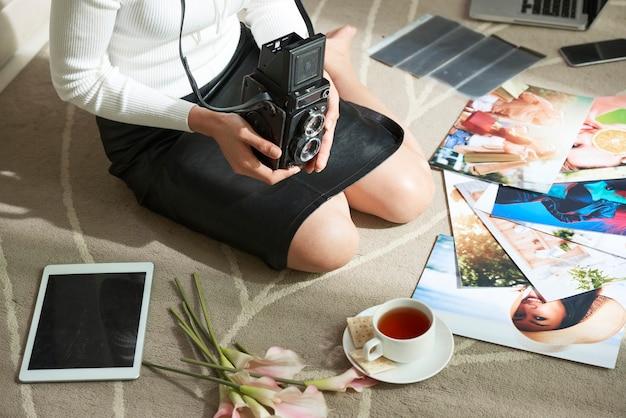 카펫에 밝은 다채로운 사진 사이 빈티지 카메라와 함께 무릎에 앉아 검은 치마에 알아볼 수 없는 여성 사진 작가의 클로즈업