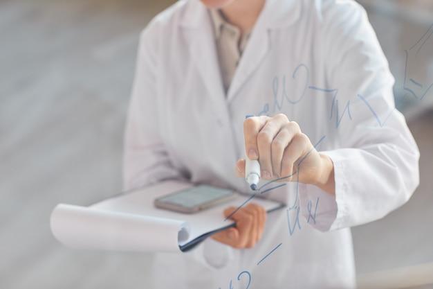 Крупный план неузнаваемой женщины-ученого, пишущей на стеклянной стене и держащей буфер обмена во время исследования в медицинской лаборатории, копией пространства