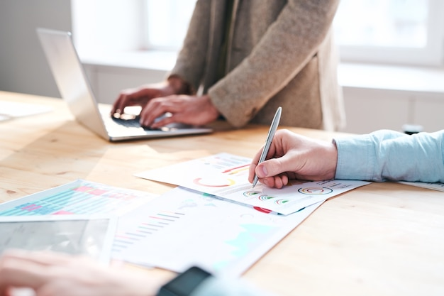 オフィスで月次レポートを分析しながらチャートにメモをとっている認識できない金融専門家のクローズアップ