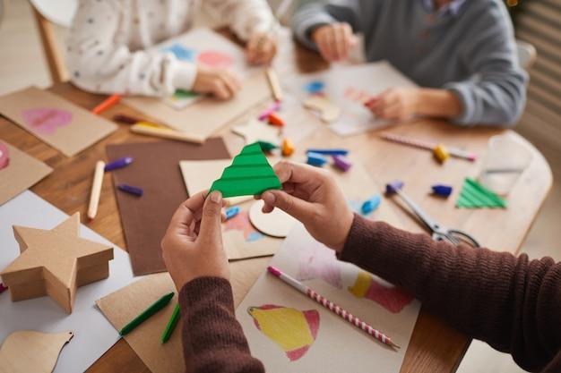 子供たちのグループとアートやクラフトプロジェクトをしながら紙のクリスマスツリーを保持している認識できない女の子のクローズアップ、コピースペース