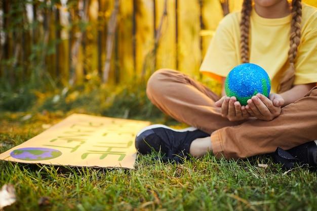 녹색 잔디에 앉아 햇빛에 야외에서 자연을 위해 항의하는 동안 손에 행성을 들고 인식 할 수없는 소녀의 닫습니다, 복사 공간 프리미엄 사진