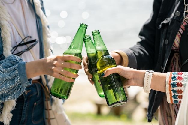 円の中に立って、屋外でビール瓶をチリンと鳴らしている認識できない女の子のクローズアップ