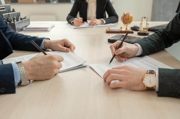 Крупный план неузнаваемых юристов в наручных часах, сидящих друг напротив друга за столом и читающих договор перед подписанием на встрече