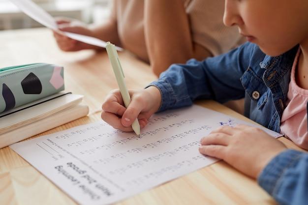 自宅で勉強しながらオンライン学校の数学のテストをしている認識できない少女のクローズアップ、コピースペース