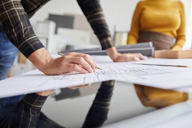 사무실에서 책상에서 작업하는 동안 인식 할 수없는 남성 건축가 도면 청사진의 닫습니다,