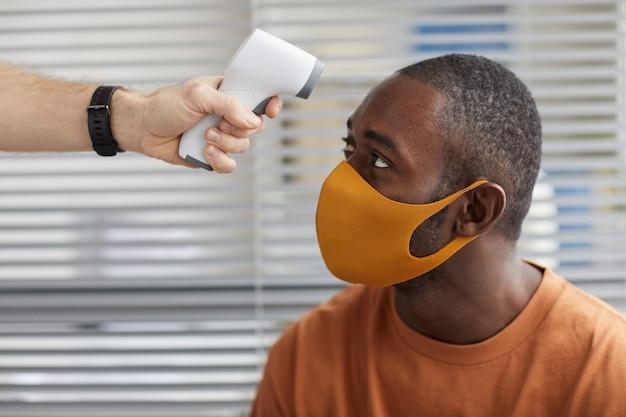 의료 클리닉에서 줄을 서서 기다리는 동안 마스크를 쓴 아프리카계 미국인 남성의 체온을 확인하는 알아볼 수 없는 남성 의사의 클로즈업