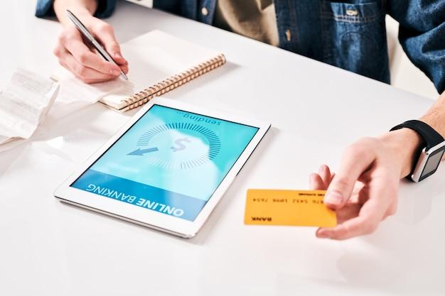 Крупный план неузнаваемого мужчины, проверяющего квитанцию и использующего приложение онлайн-банка для оплаты счета за покупку