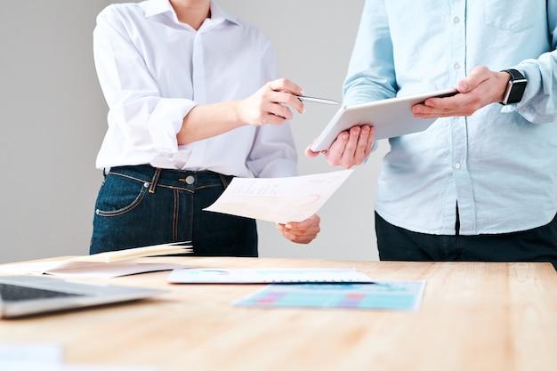 Крупный план неузнаваемого мужчины, держащего планшет во время обсуждения маркетингового плана с коллегой в офисе