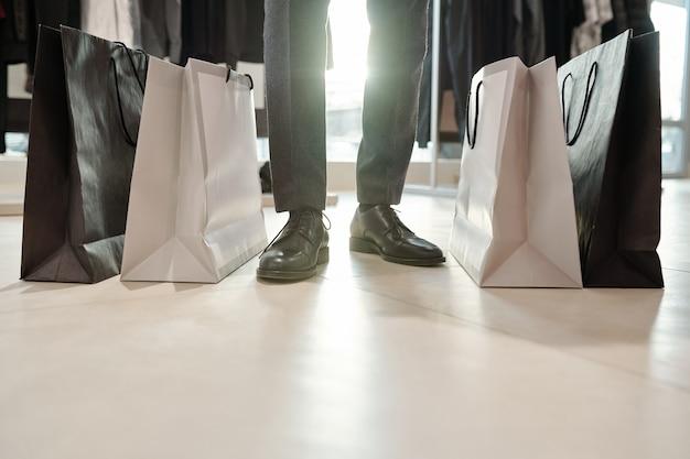 メンズストアの服の完全な買い物袋の間に立っているフォーマルな靴の認識できない男のクローズアップ
