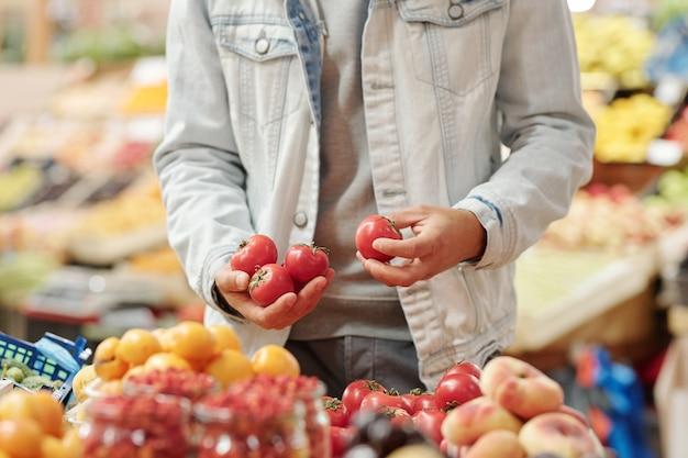 음식 카운터에 서서 유기농 시장에서 신선한 토마토를 복용하는 재킷에 인식 할 수없는 남자의 근접