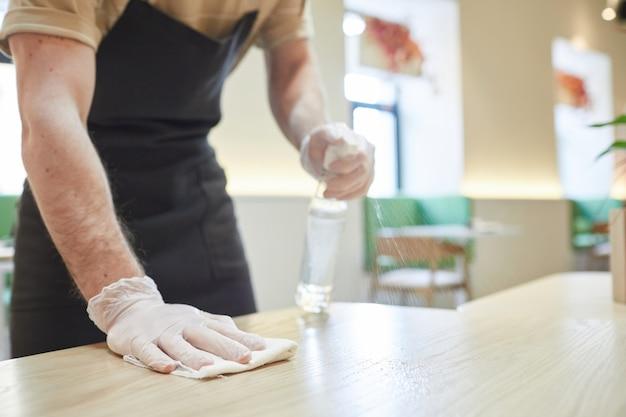 Закройте до неузнаваемости человека, дезинфицирующего столы и чистящего мебель в кафе, копируя пространство