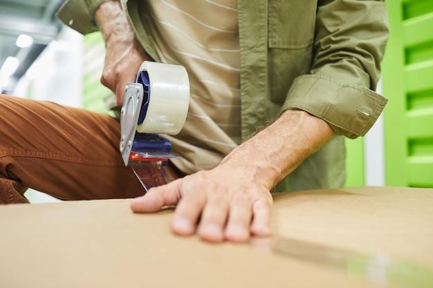 자기 저장 장치에 포장하는 동안 스카치 테이프 총으로 골판지 상자를 밀봉하는 인식 할 수없는 남자의 닫습니다, 복사 공간