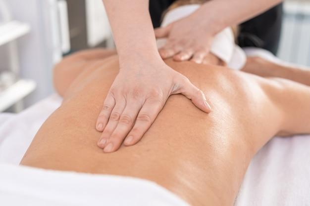 Крупный план неузнаваемого массажиста, делающего массаж спины, чтобы расслабить женщину в спа-салоне