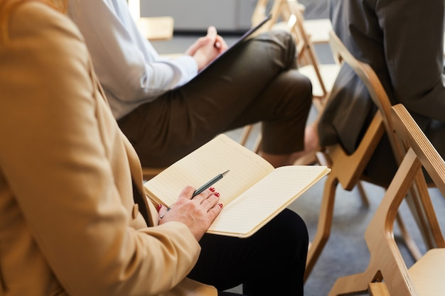 会議やセミナー中に聴衆に座っている間、開いたメモ帳を保持している認識できない成熟した実業家のクローズアップ、コピースペース